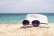 Close up of white hat and sunglasses on the beautiful sand beach as summertime concept