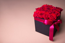 Black Box With Beautiful Red Rose Flowers Over Beige Background