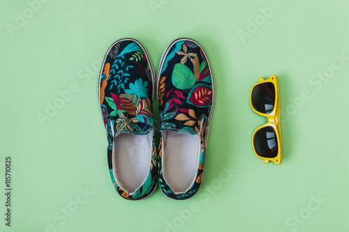Fotografie, Obraz  Flat lay fashion set: colored slippers shoes with palm and flowers print and yellow sunglasses on pastel background