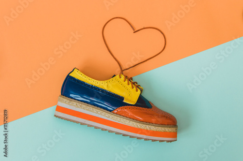 Fotografie, Obraz  Flat lay fashion set: one vintage shoe on colored background with heart of laces