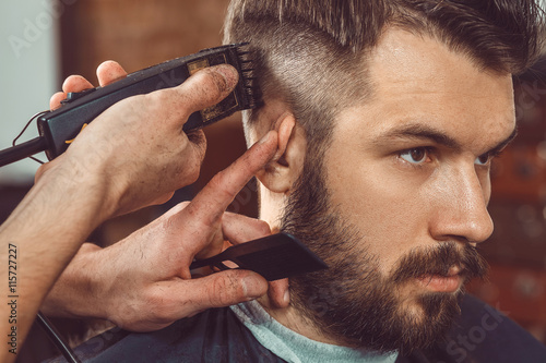 Printed kitchen splashbacks Hair Salon The hands of young barber making haircut to attractive man in barbershop