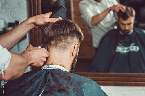 mata magnetyczna The hands of young barber making haircut to attractive man in barbershop