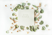 "White Wedding Or Family Photo Album With Words ""love Story"", Frame With Dry And Fresh Branches Isolated On White Background. Flat Lay, Overhead View"