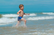 little boy child running through the sea with is tongue out