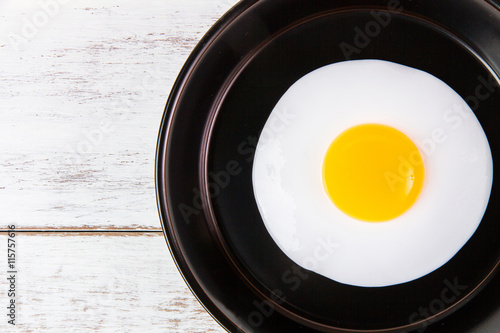 Foto auf Gartenposter Eier Fried egg in small pan with handle on blue wooden board
