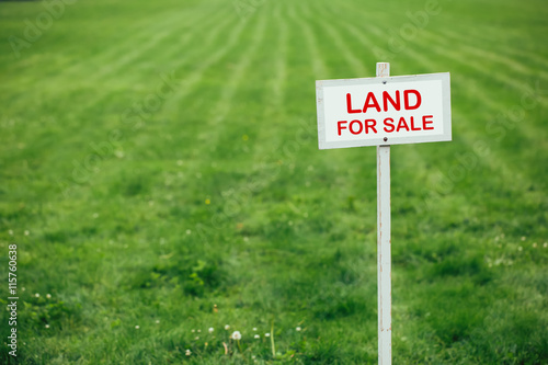 Fotografija land for sale sign against trimmed lawn background