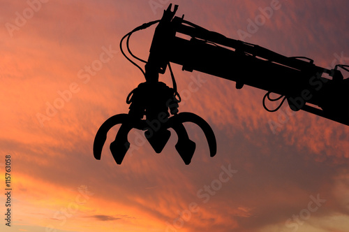 Tablou Canvas Clamshell and Hydraulic crane shillouette with evening light sky