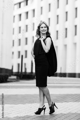 Fotografija  Black-and white portrait of business woman outside office buildings