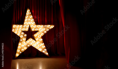 Fotografia, Obraz Photo of golden star with light bulbs on red velvet curtain on stage