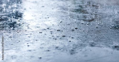 Fotografia Heavy rain drops on asphalt closeup. Cold toning.