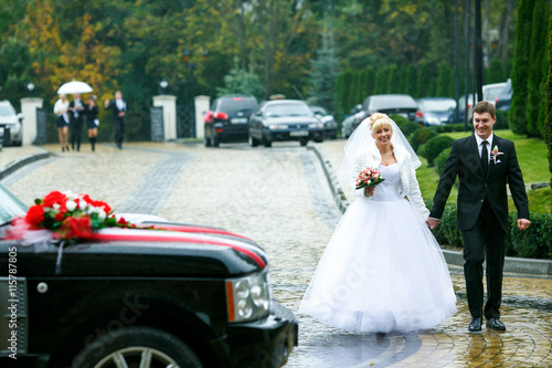 Photo  Bride and groom go to the car holding their hands together
