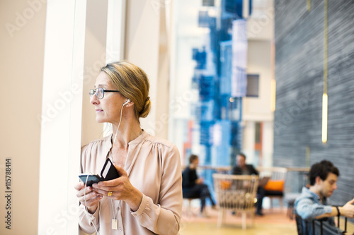 Businesswoman looking through window while listening music
