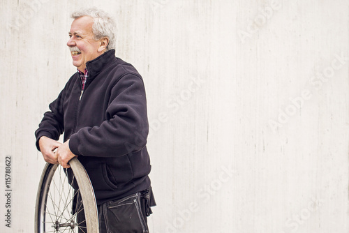 Happy senior male mechanic repairing bicycle tire outside workshop