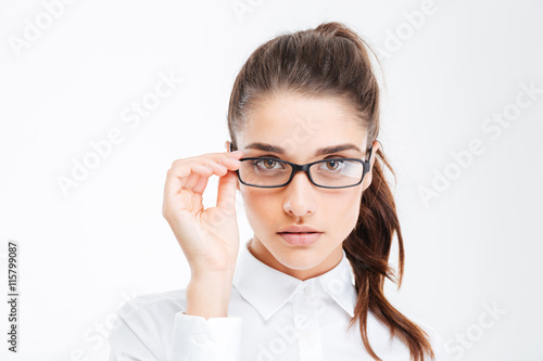 Closeup of serious beautiful young businesswoman in glasses