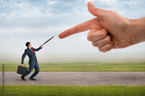 Fototapeta  giant finger pointing aggressively at a defensive businessman