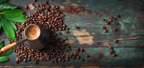 Hot coffee in a coffeepot or turk on a wooden background with coffee leaves and beans, horizontal with copy space. Top view