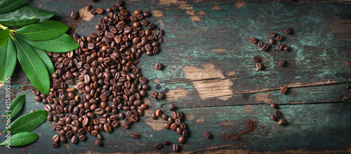 Photo sur Toile Salle de cafe Roasted coffee beans with green leaves on a vintage background, top view with copy space