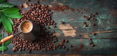 Papiers peints Café en grains Hot coffee in a coffeepot or turk on a wooden background with coffee leaves and beans, horizontal with copy space. Top view