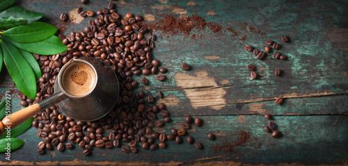 Gorąca kawa w coffeepot lub turk na drewnianym tle z kawowymi liśćmi i fasolami horyzontalnymi z kopii przestrzenią ,. Widok z góry