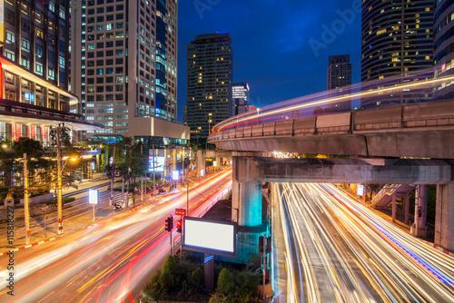 Obraz na plátně  Traffic light and sky train in busy light trails at night - Bangkok, Thailand