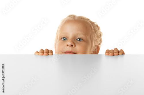Fotografiet  Funny little girl hiding behind white table