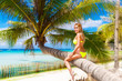 Young beautiful girl in bikini on the palm tree on a tropical be