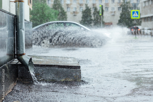 Valokuvatapetti Rain water flowing from metal drainpipe during a flood