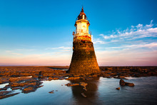 Plover Scar Lighthouse At Cockerham On Morecambe Bay In The UK. The Lighthouse Has Been Damaged By The Sea. At Sunset.