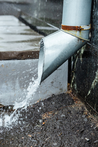 Fotografia, Obraz  Closeup rainwater flow from the drainpipe installed on brick wall
