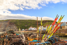 STAITHES, ENGLAND - JULY 12: Lobster Pots Stacked On The Quayside, Looking Out To Staithes Harbour. In Staithes, North Yorkshire, England. On 12th July 2016.