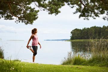 Woman stretching by lake