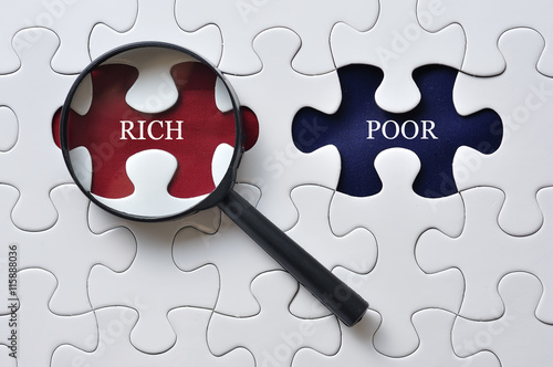 Photo Magnifying Glass On Missing Puzzle with RICH/POOR Word, Antonym Concept and Se