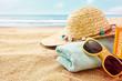 Towel, hat, sunglasses and lotion at ocean beach