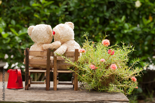 fototapeta na lodówkę lovely teddy bear and watering can in the garden of love, conce