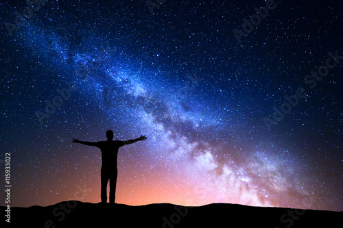 Aluminium Prints Universe Night landscape with Milky Way. Silhouette of a standing young man with raised up arms on the mountain. Beautiful Universe. Travel background with blue night starry sky