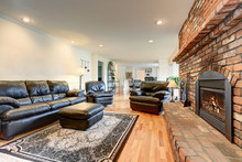 Luxury Living Room Interior With Black Leather Sofa Set And Brick Fireplace.