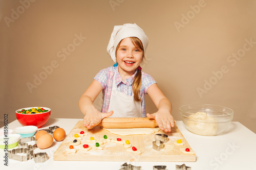 Poster Cuisine Girl playing baker, flattening dough for cookies