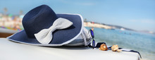 Hat On The Beach With Bag, Sunglasses, Shells And Towel