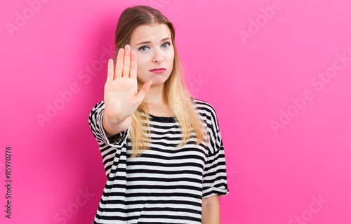 Fotografie, Obraz  Young woman making a stop pose on a pink background