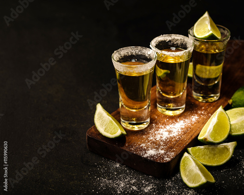 Cuadros en Lienzo Mexican Gold Tequila with lime and salt on wooden table, selective focus