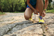 young woman trail runner tying shoelaces in forest