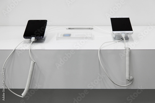 Photo Two  smartphones on a white showcase with  antitheft system