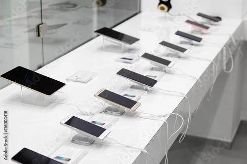 Fototapeta Kilka smartfonów i tabletów z urządzeniami antykradzieżowymi w sklepie