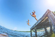 The Children, A Boy And A Girl Jumping From A Wooden Pier In The Water.Toning