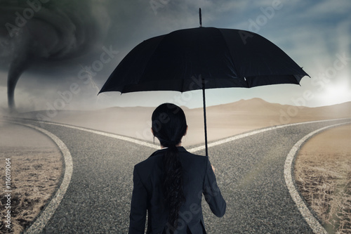 Worker with umbrella looking at two roads