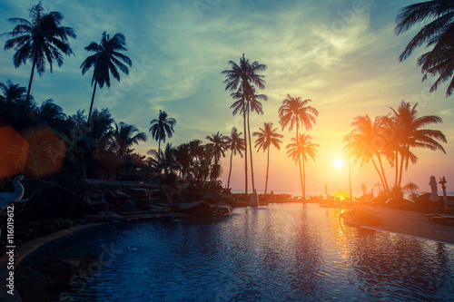 Fototapety, obrazy: Sunset on the tropical coast, the silhouettes of the palm trees and pool.