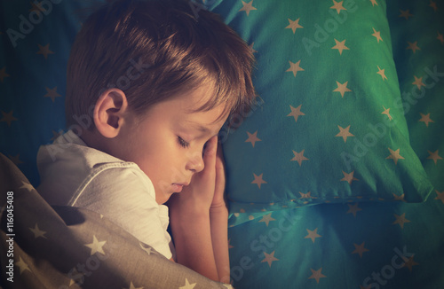Adorable little boy sleeping in bed