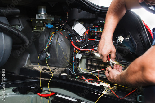 Fotografía  Electrician works with electric block in car