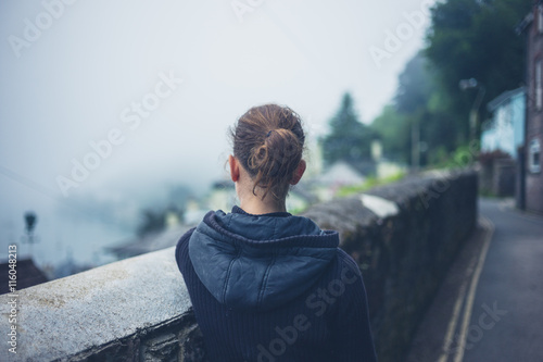Fotomural  Young woman standing by wall in fog