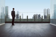 Businessman standing on a roof and looking at city